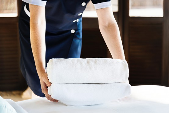 A housekeeper putting new towels on bed.